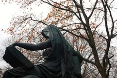 Sitting and reading. A statue of woman in cloak sitting and reading big book in a park in Berlin, Germany Stock Image