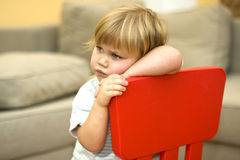 Sitting on red chair sad little girl Royalty Free Stock Photo