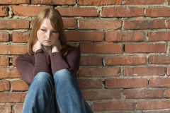Sitting redhead woman in front of brick wall Stock Photography