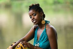 Sitting by the river. African American woman sits and relaxes by the river front stock images