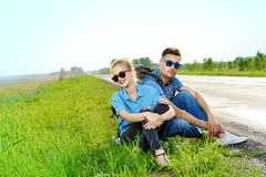Sitting by the road. Hitchhiking couple. Happy young people sitting by the highway Royalty Free Stock Photos