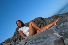 Sitting on rock. African-American female sitting on rock by ocean Stock Photo