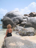 Sitting on a Rock. A woman sitting on a boulder at Devil's Bay at Virgin Gorda, British Virgin Islands. If you can, please leave a comment about what you are stock photos