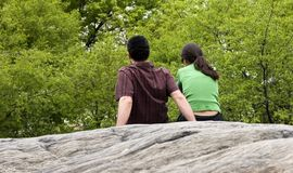 Sitting on the rock. Young couple sitting on the rock in the park royalty free stock photos