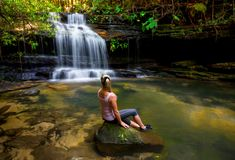 Woman at waterfall and swimming hole in bushland wilderness. Sitting on a rock in the swimming hole enjoyin the dappled sun filtering through lush green royalty free stock images