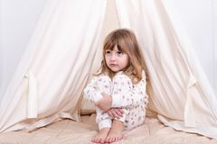 Sitting sad girl. Small sad girl sits at a tent in pajamas and hugs her knees Royalty Free Stock Photography