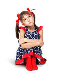 Sitting sad, thoughtful child girl with red bows, isolated on wh Stock Photo