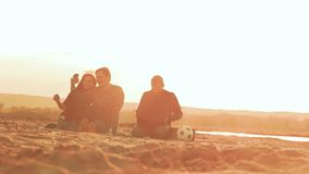 Sitting on the sand beach, two men and a girl laugh slow motion video. At sunset the sun on the beach sand sit two men and girl with laptops couple doing selfie stock video