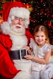 Sitting with santa claus. A happy young girl is with Santa Claus at home. Merry Christmas and Happy New Year royalty free stock image