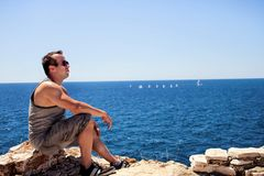 He is sitting by the sea and thinking about life. Background is the blue sky and the boats sailing on the sea Stock Photography