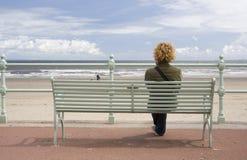 Sitting at Seafront. Young woman looking at something along the sea front, at Portobello, Edinburgh, Scotland Stock Photos