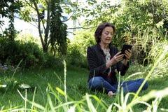 Mature woman reading an e-book in the garden. Senior woman sitting on the ground in the garden reading an e-book with an e-reader Stock Images