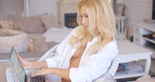 Sitting Sexy Woman with Laptop Showing Cleavage. Close up Sitting Sexy Blond Woman with Laptop Computer at the Living Room Showing her Cleavage Stock Photos