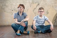 Sitting side by side on the floor. Warm regards mom and son Stock Photo