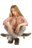 Sitting on skateboard Stock Images