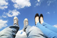Sitting in the sky. Legs dangling in the blue sky with clouds stock photos