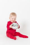 Sitting smiling baby in red with party ball Royalty Free Stock Photo