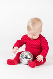 Sitting smiling baby in red with party ball Royalty Free Stock Photography