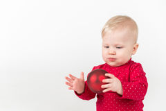 Sitting smiling baby in red with party ball Royalty Free Stock Image