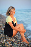 Sitting smiling beautiful woman on stone seacoast Stock Photo
