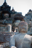 Sitting and smiling Buddha in stone at Borobudur Stock Image