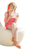 Sitting smiling girl with orange headphones and white tablet pc Royalty Free Stock Photos