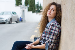 Sitting smiling young woman in the street stock photos