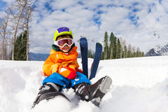 Sitting on snow boy in ski mask and helmet Royalty Free Stock Photo