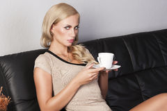 Sitting on sofa drinking from a cup Royalty Free Stock Photo