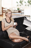 Sitting on sofa drinking from a cup Stock Photos