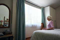 Sitting in solitude. A depressed elderly widow sitting on her bed looking out the window Stock Photos