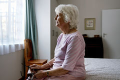 Sitting in solitude. A solemn elderly woman sitting on her bed dealing with depression Stock Photography