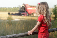 Sitting spectator girl watching over working combine harvester Stock Photos