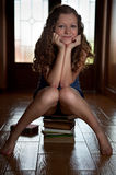 Sitting on stack of books Royalty Free Stock Photography