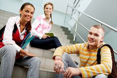 Sitting on stairs. Portrait of three teens sitting on stairs and looking at camera in college Royalty Free Stock Photography
