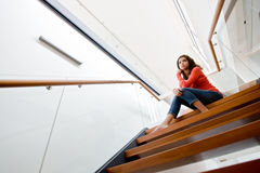 Sitting On Stairs. A young woman sitting on the stairs at home Stock Photo