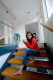 Sitting On Stairs. A young woman sitting on the stairs at home royalty free stock photography