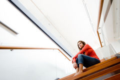 Sitting On Stairs. A young woman sitting on the stairs at home stock image