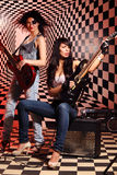 Sitting and standing women play electric guitar and sing Stock Photos