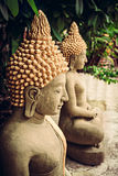 Sitting stone Buddha statues at temple area. Among green foliage Royalty Free Stock Photography