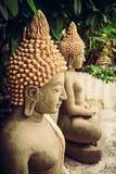 Sitting stone Buddha statues at temple area. Among green foliage royalty free stock photography