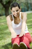 Sitting Stretch. A young woman stretching in the park outside stock images