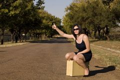 Sitting on suitcase thumb Stock Photography