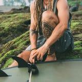 Sitting surfer with tattoos, dreadlocks close up stock photos