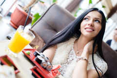 Sitting in sushi restaurant or coffee shop beautiful sexy brunette girl young woman having fun happy smiling & looking up Royalty Free Stock Images
