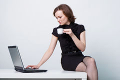Sitting on the table an girl with a laptop and a cup of coffee Stock Image