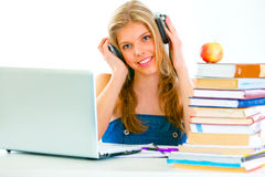 Sitting at table girl listening audio lessons Stock Photo