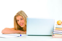 Sitting at table girl looking out from laptop Stock Image
