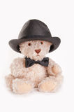 Sitting teddy bear with bow tie and hat. A cute, sitting teddy bear wearing a bow tie and hat Stock Photography