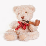 Sitting teddy bear with red bow and wooden pipe. A sitting teddy bear with a red bow and wood pipe isolated on white Stock Photos